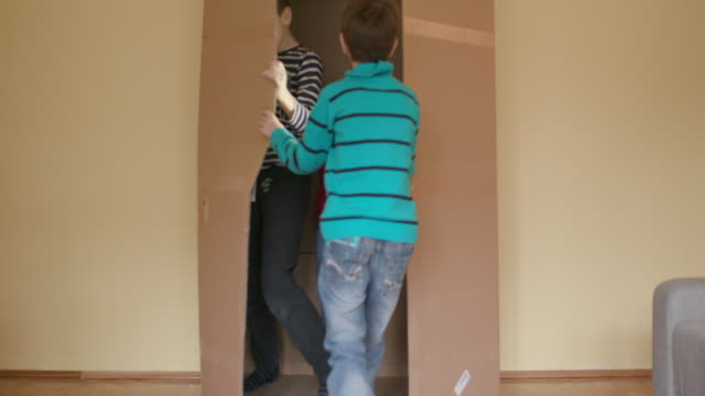 boys hiding in cardboard box - carton stock videos & royalty-free footage