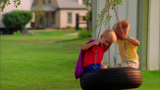boys in capes spin on a tire swing. - schwindelig stock-videos und b-roll-filmmaterial