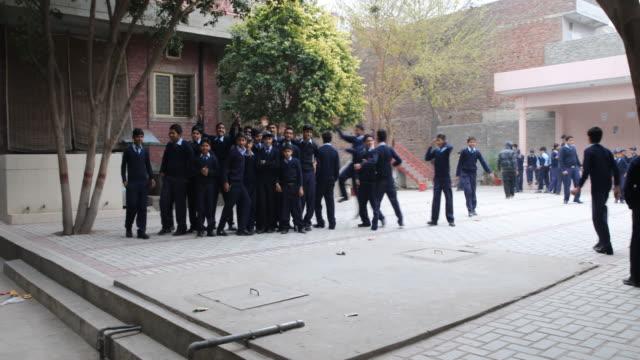 stockvideo's en b-roll-footage met boys in middle and high school age wearing school uniform posing for the camera during class break. - alleen jongens