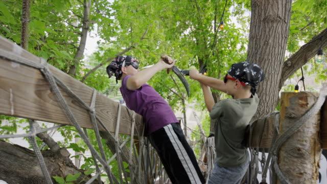 boys in pirate costumes sword fighting on tree bridge / provo, utah, united states - provo stock videos & royalty-free footage