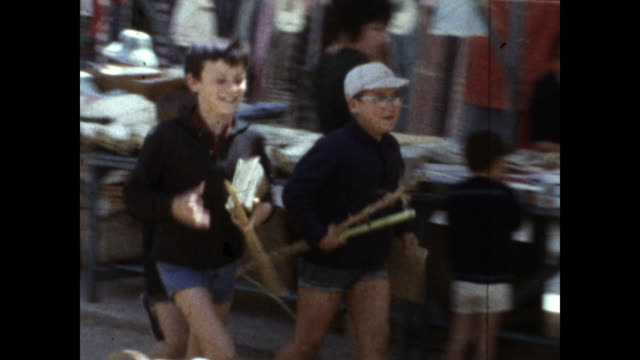 boys in shorts running and laughing through the street full of vendors; one boy looks and smiles at the camera - running shorts stock videos & royalty-free footage