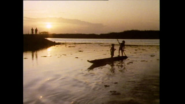 boys in silhouette paddle canoe in papua new guinea; 1985 - isole del pacifico video stock e b–roll