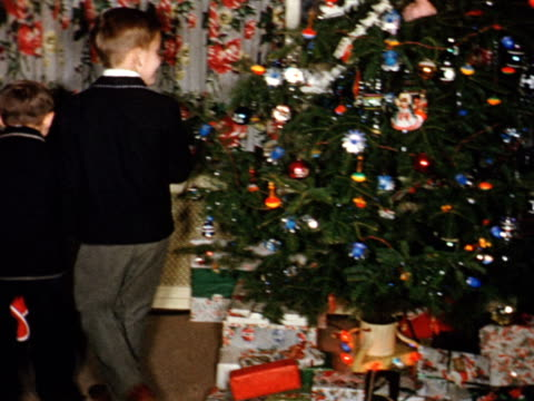 stockvideo's en b-roll-footage met 1955 home movie boys in suits hanging christmas stockings and playing with baby sisiter / toronto, canada - 1955