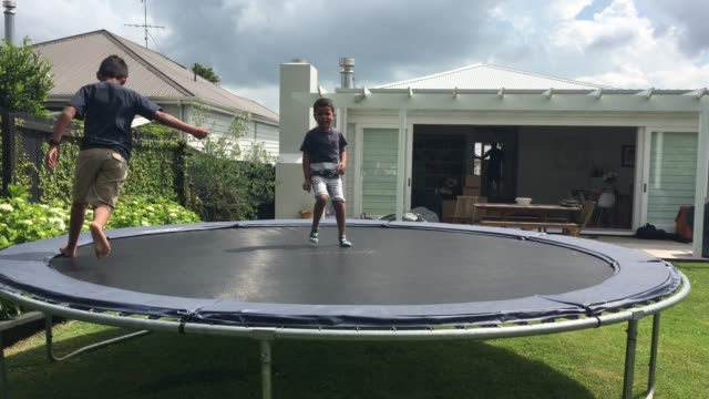 boys jumps on trampoline in their home backyard - pacific islander family stock videos & royalty-free footage