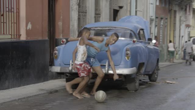 stockvideo's en b-roll-footage met boys kicking ball in street - cuba