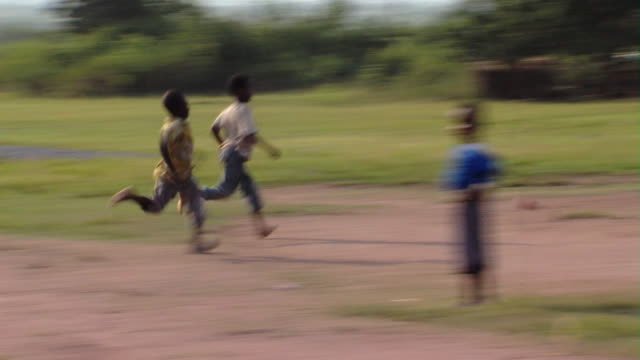 MS PAN ZI Boys kicking ball on dirt field, Tamale, Ghana
