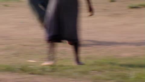 ms swish pan boys kicking ball on dirt field, tamale, ghana - swish pan stock videos & royalty-free footage