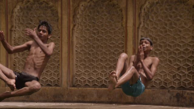 boys leap into pool at galtaji temple, jaipur, india - jumping stock videos & royalty-free footage