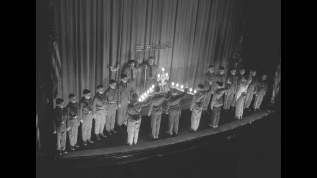 boys line up on stage with be prepared on curtain / light bulbs on candelabra are lit for ceremony they follow american flag off stage - boy scout stock videos and b-roll footage