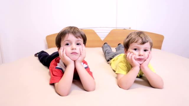 stockvideo's en b-roll-footage met jongens kijken camera. - op de buik liggen
