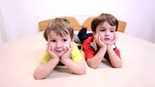 stockvideo's en b-roll-footage met jongens kijken camera - op de buik liggen
