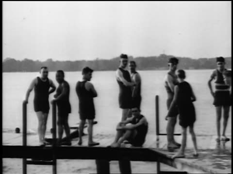 b/w 1915 boys + men on dock / some dive off board into lake/river / newsreel - swimming costume stock videos and b-roll footage