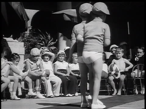 B/W 1936 2 boys modeling matching outfits in children's fashion show / Miami Florida / newsreel