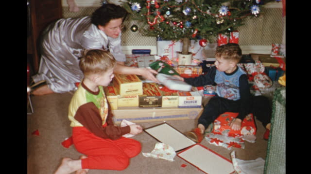 1954 home movie boys, mother and grandmother opening christmas gifts / toronto, canada - home movie stock videos & royalty-free footage