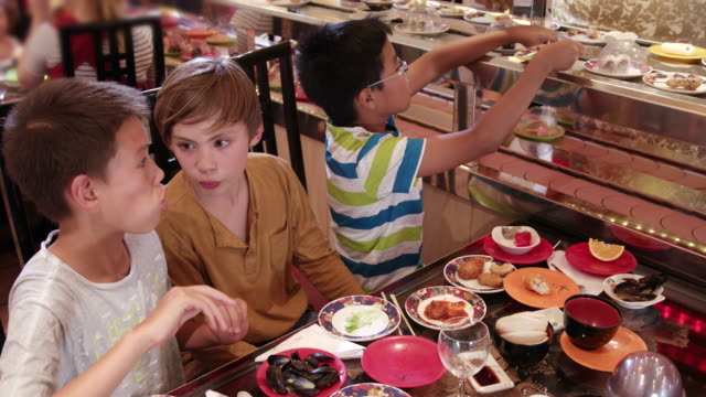 3 boys of diverse ethnicities enjoying themselves and all you can eat asian food in running sushi restaurant - children only stock videos & royalty-free footage
