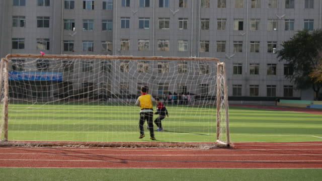 Boys of Korean nationality are playing football on an elementary school campus