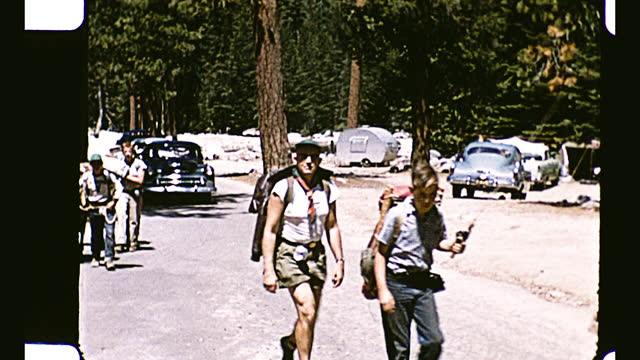 boys of various age carrying backpacks and camp gear walking across the camera, forest and cars parked in the background; boys with backpack leading... - camping stock videos & royalty-free footage