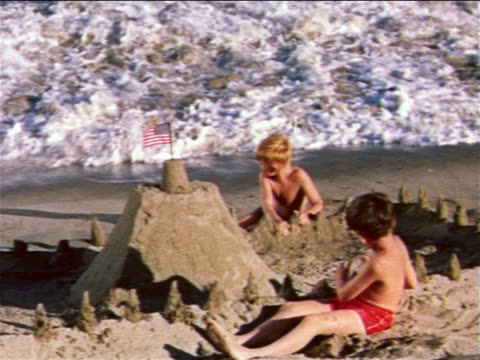 1959 2 boys on beach building sand castle with american flag on top / wave washes over it / industrial - prelinger archive stock-videos und b-roll-filmmaterial