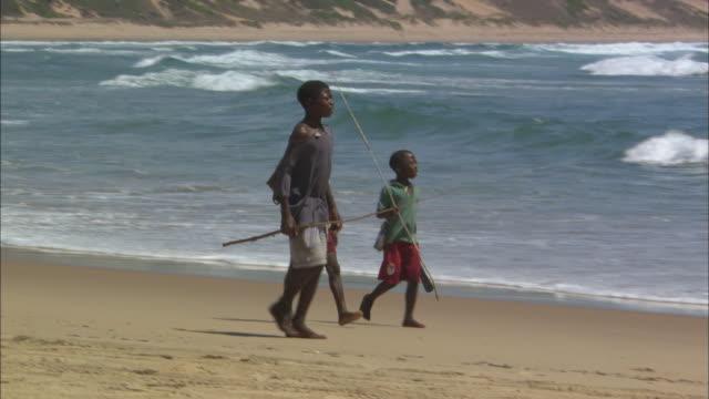 vídeos de stock e filmes b-roll de boys on beach, three with fishing poles, walking, mozambique  - moçambique