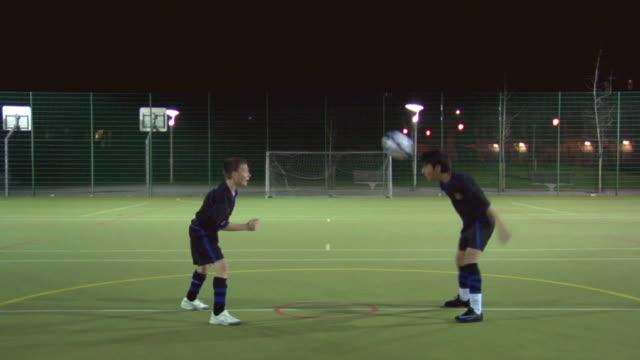 ws boys (14-15) on soccer field heading ball, london, uk - geköpft stock-videos und b-roll-filmmaterial