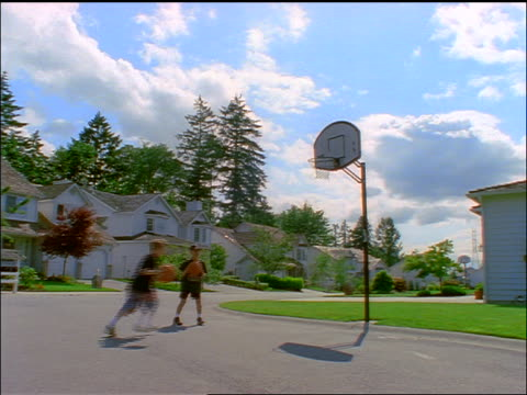 2 boys on suburban street playing basketball - lockdown viewpoint stock videos & royalty-free footage