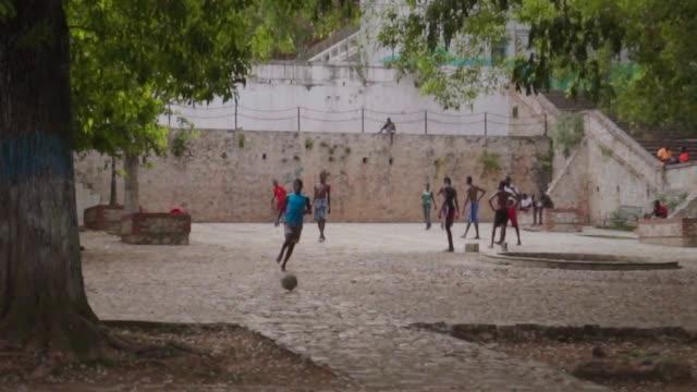 vídeos y material grabado en eventos de stock de boys play barefoot soccer in courtyard - descalzo