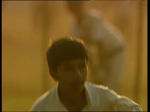 boys play cricket in park under glow of hazy sunset calcutta - westbengalen stock-videos und b-roll-filmmaterial