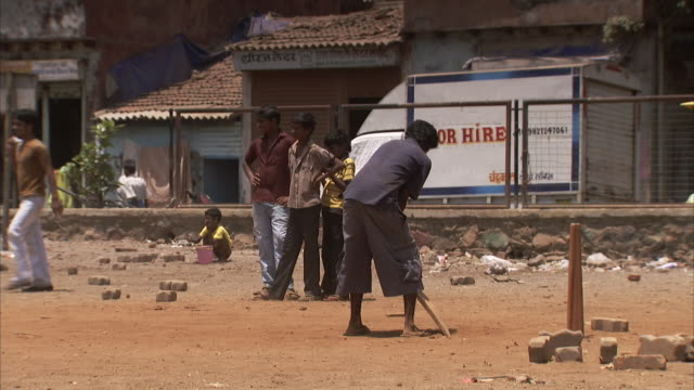 boys play cricket on a dirt patch in india. - cricket video stock e b–roll