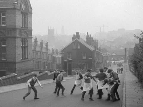 Boys play football on a road outside a school