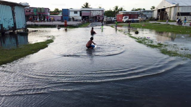 boys play in floodwaters occurring around high tide in a low lying area near the airport on november 27 2019 in funafuti tuvalu the lowlying south... - isole del pacifico video stock e b–roll