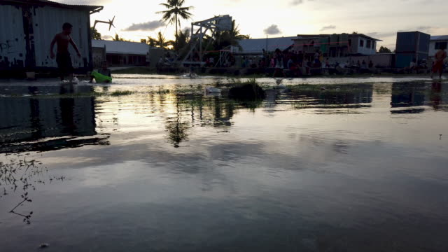 boys play in floodwaters occurring around high tide in a low lying area near the airport on november 27, 2019 in funafuti, tuvalu. the low-lying... - pacific islands stock videos & royalty-free footage