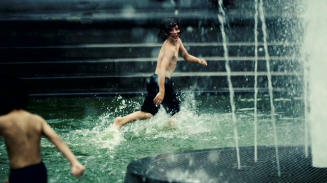 boys play in the fountain pool in manhattan's washington square park. - fountain stock videos and b-roll footage
