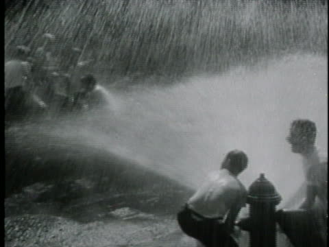 boys play in the water from a fire hydrant on a hot day in 1945. - 水かけっこ点の映像素材/bロール