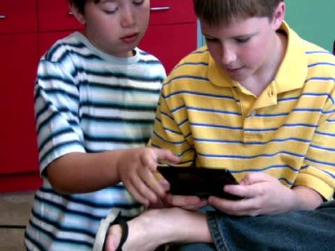 boys play mobile video games - handheld video game stock videos & royalty-free footage