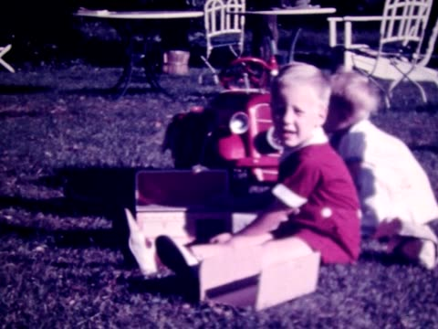 1938 boys play with new, red, Fire Chief fire engine