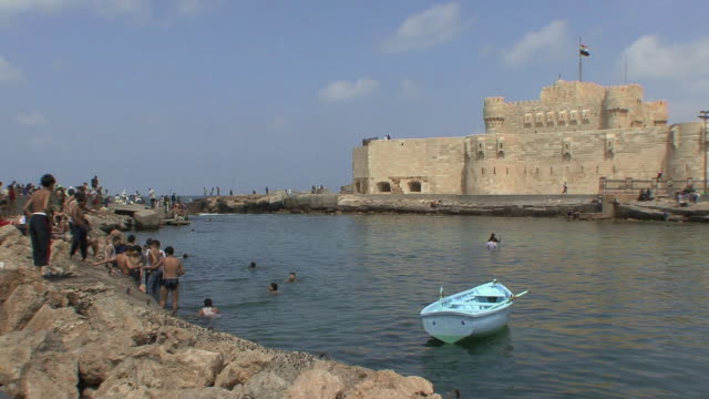WS Boys playing and jumping in water on Fort Qaitbay pier, Alexandria, Egypt