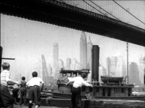 b/w 1945 boys playing by brooklyn bridge / tugboat + manhattan skyline in background / educational - brooklyn bridge stock videos & royalty-free footage