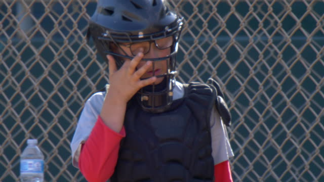 boys playing catcher and catching in a little league baseball game. - slow motion - goodsportvideo stock videos and b-roll footage