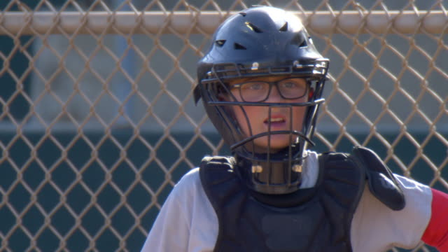 Boys playing catcher and catching in a little league baseball game. - Slow Motion