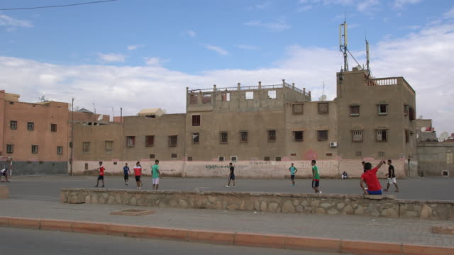 boys playing football, not far from the the medina of marrakesh, morocco - the history boys stock videos & royalty-free footage