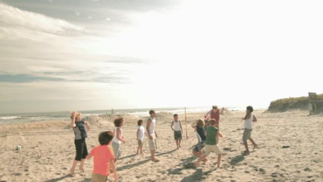 Boys playing football on beach, ball kicked into air