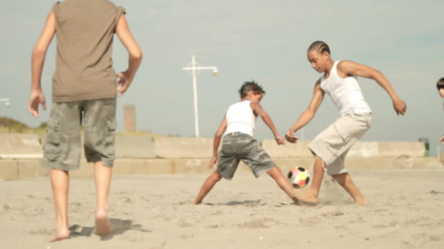 boys playing football on beach, kick off - native american ethnicity stock videos and b-roll footage