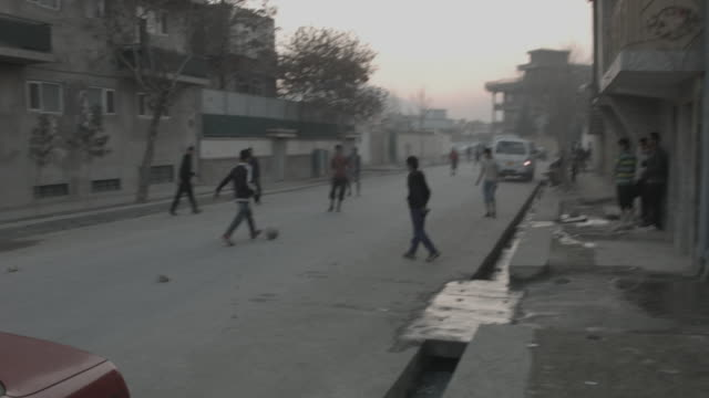 boys playing football on kabul city streets - kabul stock videos & royalty-free footage