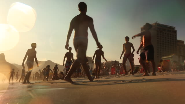 Boys playing football on the beach