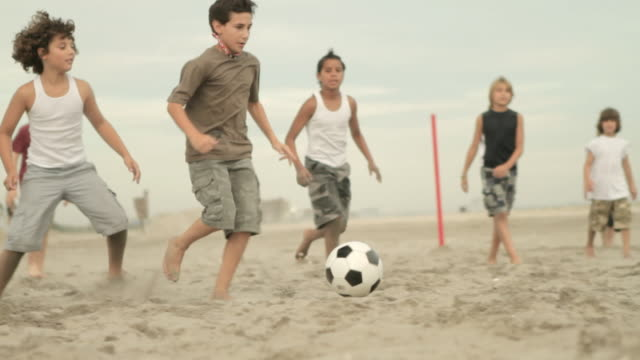 Boys playing game of football on beach