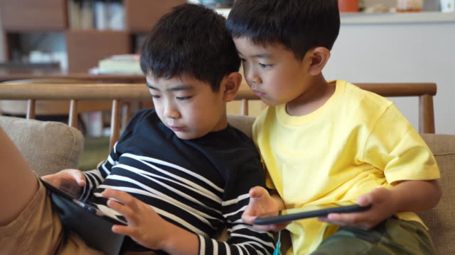 boys playing game with smartphone and tablet - childhood stock videos & royalty-free footage
