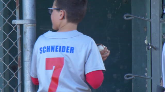 boys playing in a little league baseball game entering dugout. - slow motion - dugout stock videos & royalty-free footage