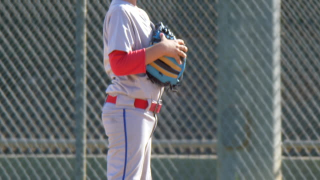 boys playing in a little league baseball game outfielder wearing 7 and a red hat. - slow motion - baseballmütze stock-videos und b-roll-filmmaterial