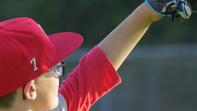 Boys playing in a little league baseball game outfielder wearing 7 and a red hat. - Slow Motion