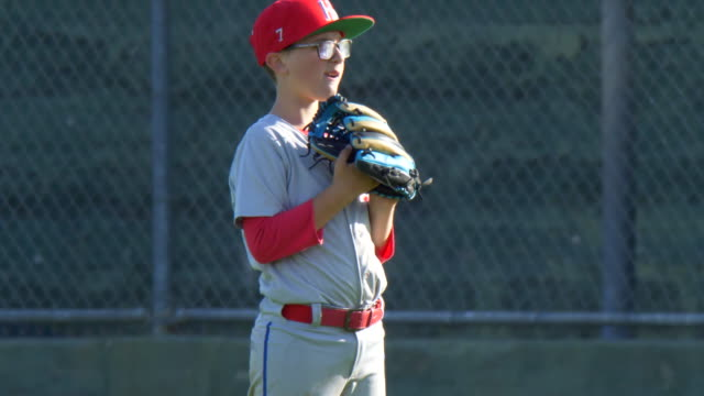 boys playing in a little league baseball game outfielder wearing 7 and a red hat. - slow motion - number 7 stock videos & royalty-free footage
